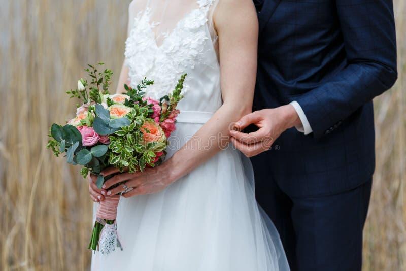 Noiva elegante no vestido branco com o laço que guarda o ramalhete nupcial de fotografia de stock royalty free
