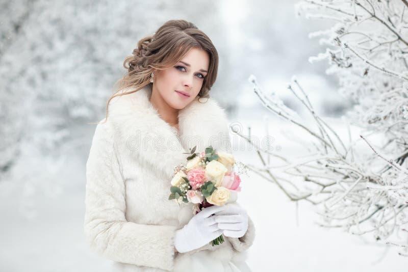 Noiva em um casaco de pele branco em uma rua coberto de neve fotografia de stock