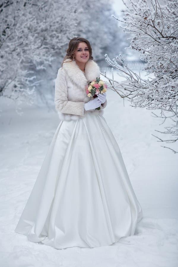 Noiva em um casaco de pele branco em uma rua coberto de neve imagem de stock royalty free