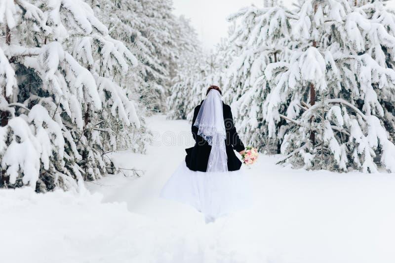 A noiva em um casaco de pele em uma floresta nevado do pinho do inverno imagens de stock royalty free