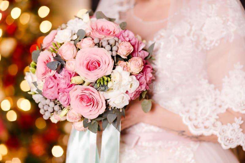 A noiva em um véu guarda um ramalhete bonito de rosas delicadas As luzes no fundo imagem de stock royalty free