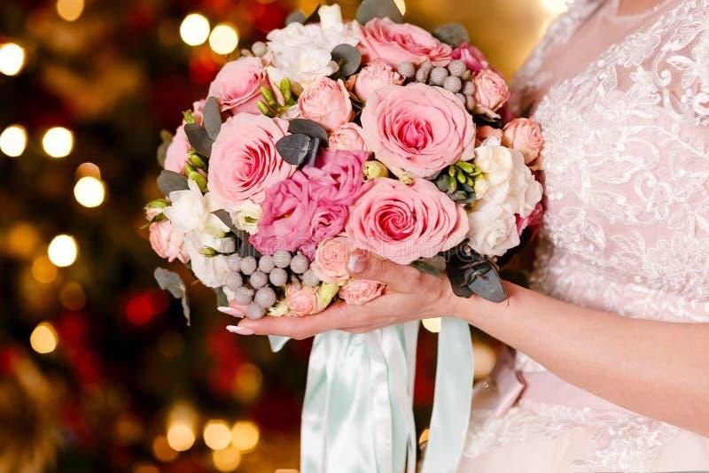 A noiva em um véu guarda um ramalhete bonito de rosas delicadas As luzes no fundo Tratamento de mãos francês em pregos ` S das mu foto de stock