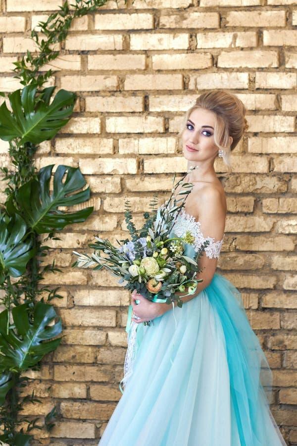 Noiva em um vestido bonito de turquesa em antecipação ao casamento Louro no verde de mar do vestido do laço com um ramalhete Noiv imagens de stock royalty free