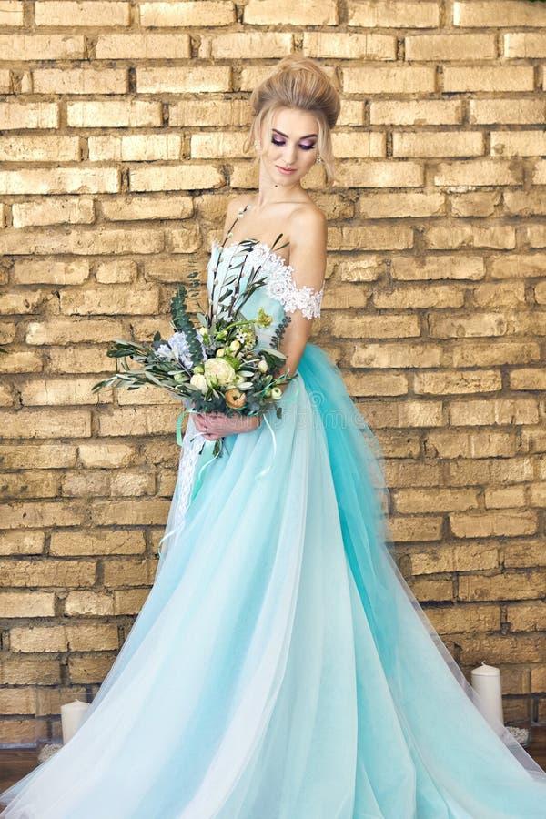 Noiva em um vestido bonito de turquesa em antecipação ao casamento Louro no verde de mar do vestido do laço com um ramalhete Noiv fotos de stock royalty free