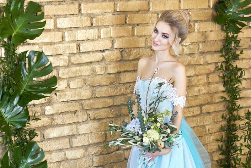 Noiva em um vestido bonito de turquesa em antecipação ao casamento Louro no verde de mar do vestido do laço com um ramalhete Noiv imagens de stock