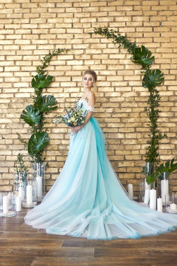 Noiva em um vestido bonito de turquesa em antecipação ao casamento Louro no verde de mar do vestido do laço com um ramalhete Noiv fotos de stock