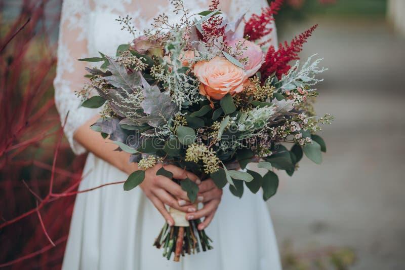 A noiva em um vestido branco é estando e realizando nas mãos um ramalhete das flores e dos verdes com uma fita foto de stock
