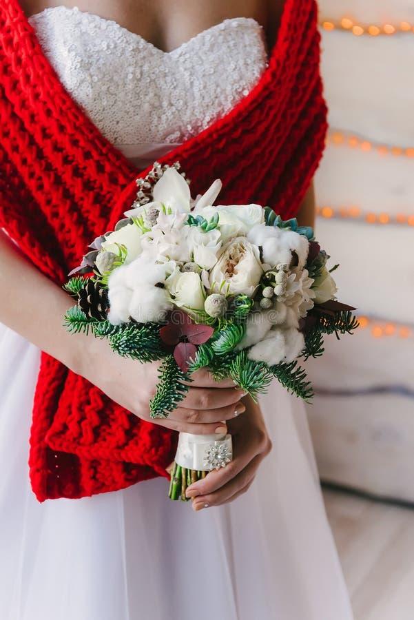 Noiva em um vestido branco e em um lenço vermelho com ramalhete imagens de stock royalty free