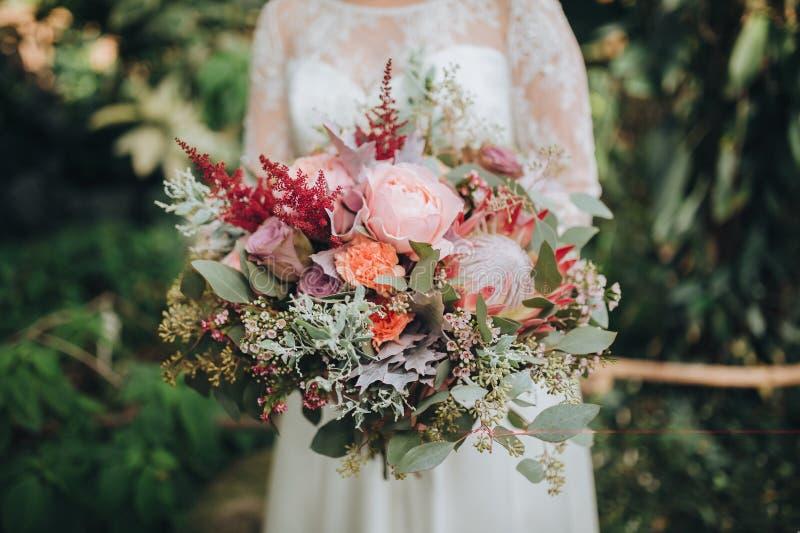 A noiva em um vestido branco que está em um fundo verde e está guardando um ramalhete do casamento das flores e dos verdes com fi fotos de stock royalty free