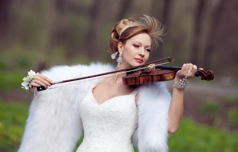 Noiva em um vestido de casamento com um violino fotos de stock royalty free