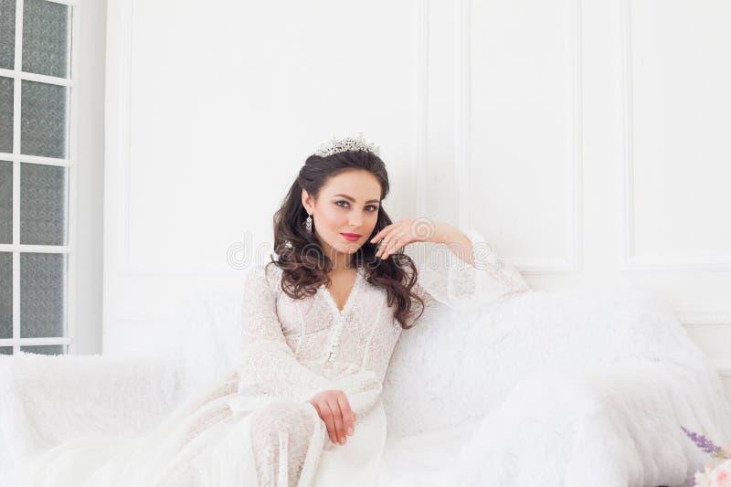 A noiva em um vestido de casamento com uma coroa que senta-se em um sofá branco imagens de stock