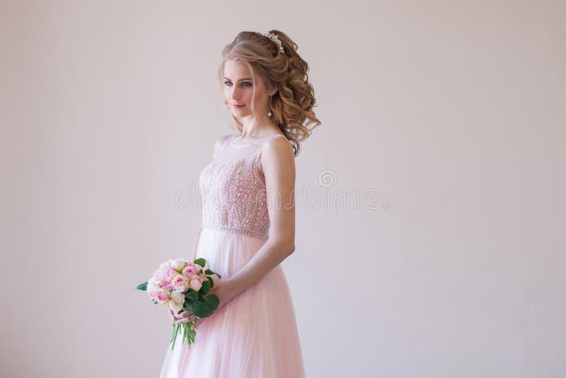 Noiva em um vestido de casamento e em um ramalhete cor-de-rosa das flores imagem de stock royalty free