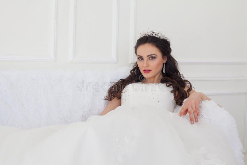 A noiva em um vestido de casamento e em uma coroa senta-se no salão branco imagem de stock royalty free