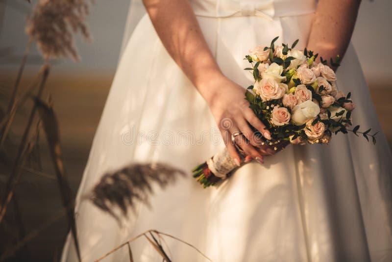A noiva em um vestido de casamento elegante guarda um ramalhete bonito de flores diferentes e das folhas verdes Tema do casamento fotos de stock royalty free