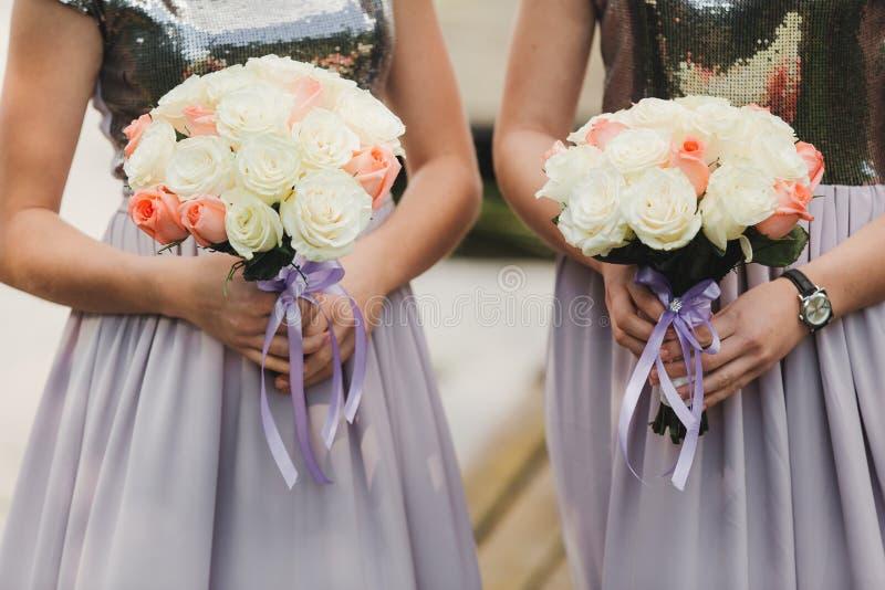 A noiva em um vestido de casamento elegante guarda um ramalhete bonito de flores diferentes e das folhas verdes Tema do casamento foto de stock royalty free