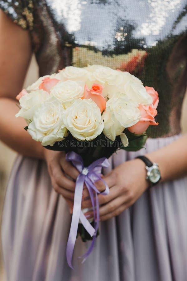 A noiva em um vestido de casamento elegante guarda um ramalhete bonito de flores diferentes e das folhas verdes Tema do casamento imagem de stock