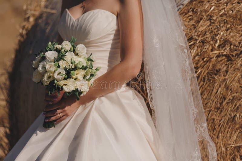 A noiva em um vestido de casamento elegante guarda um ramalhete bonito de flores diferentes e das folhas verdes Tema do casamento imagens de stock royalty free