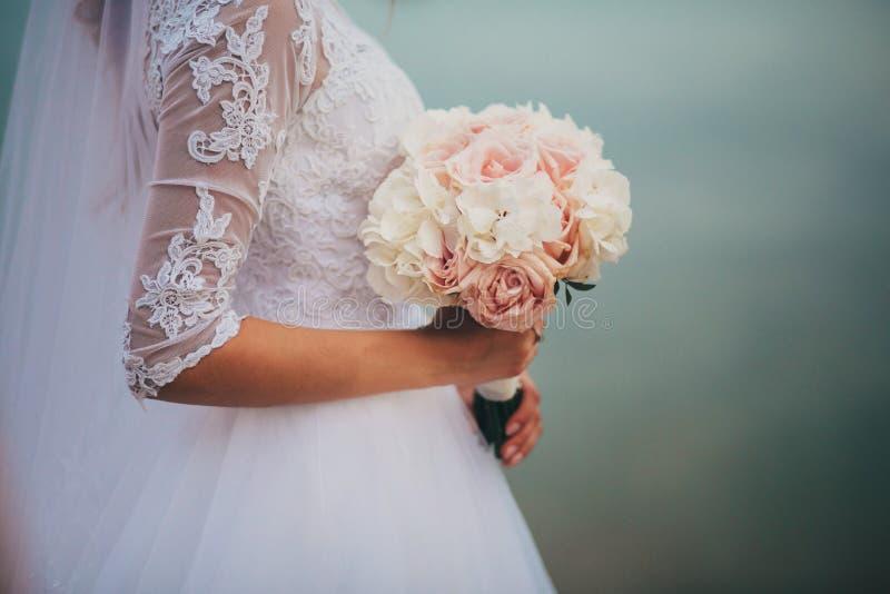 A noiva em um vestido de casamento elegante guarda um ramalhete bonito de flores diferentes e das folhas verdes Tema do casamento imagens de stock