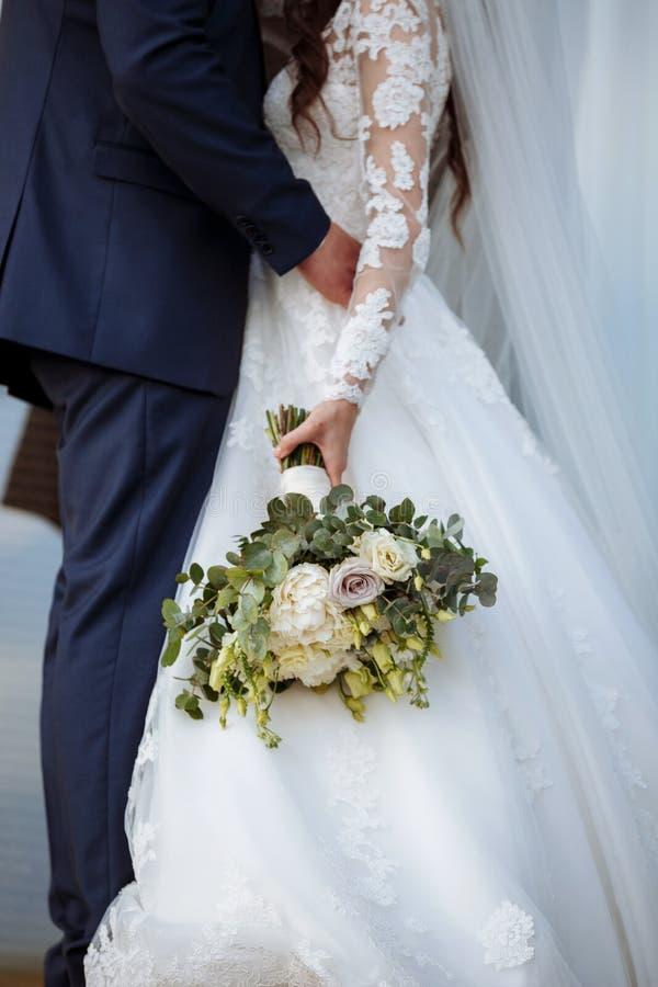A noiva em um vestido de casamento elegante guarda um ramalhete bonito de flores diferentes e das folhas verdes Tema do casamento foto de stock