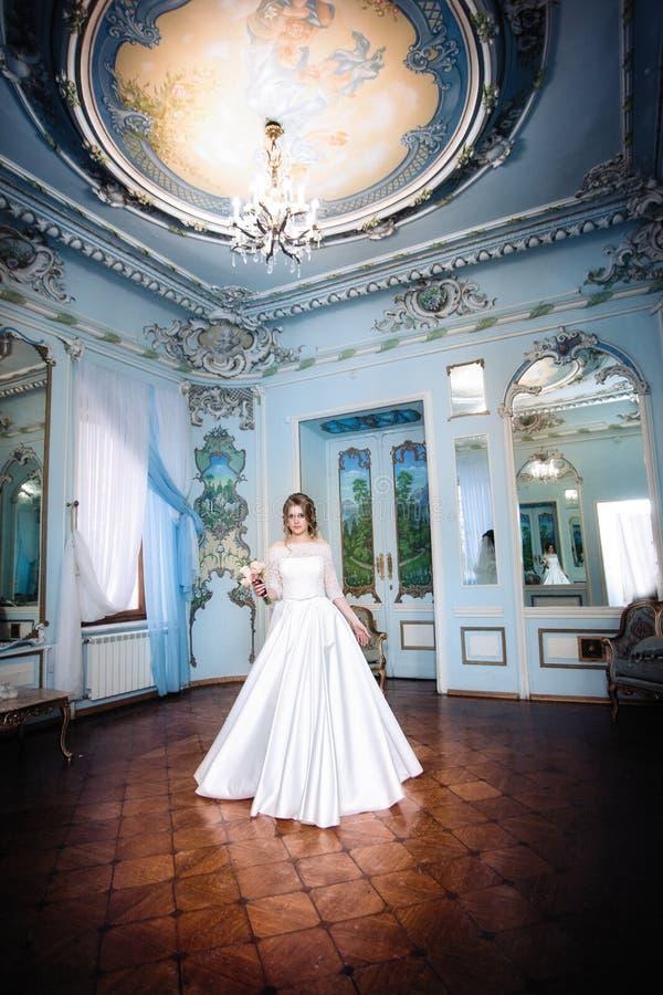 Noiva em uma sala bonita grande com um candelabro fotos de stock royalty free