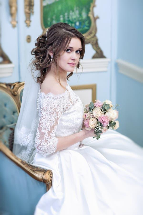 Noiva em uma sala bonita em uma poltrona azul fotografia de stock royalty free