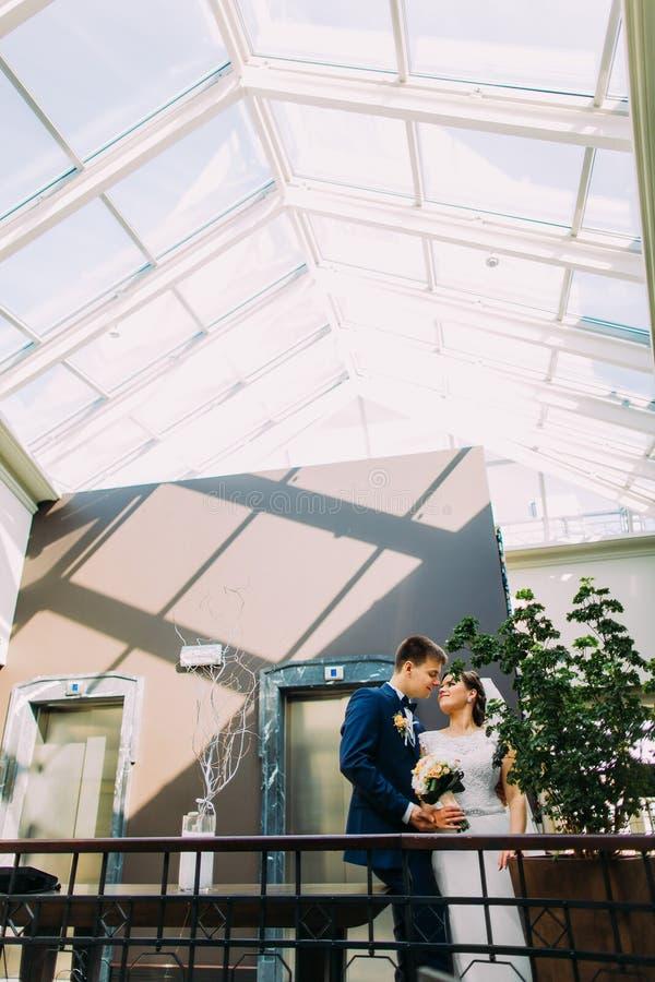 Noiva encantador e noivo considerável que olham entre si com a entrada do hotel como o fundo fotos de stock