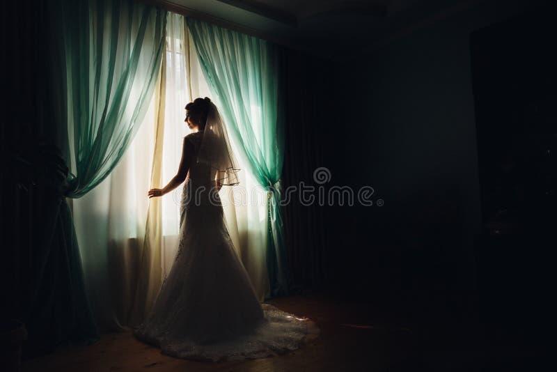 A noiva está antes da janela coberta com as cortinas verdes foto de stock