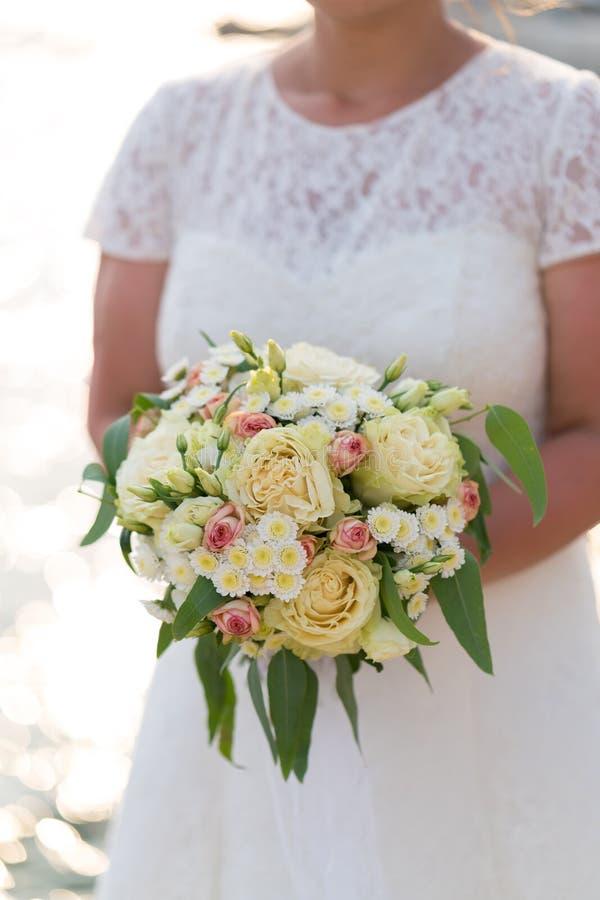 A noiva está guardando um rosa e um ramalhete bege do casamento de flores frescas e de eucalipto foto de stock royalty free