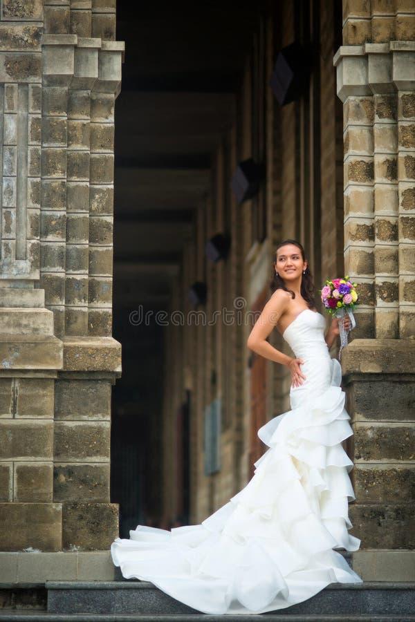 A noiva está na parede de pedra em um vestido de casamento branco bonito com um ramalhete das flores fotos de stock royalty free