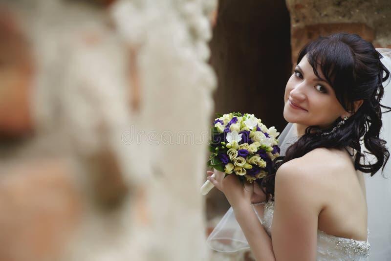 A noiva está sentando-se nas ruínas e está guardando-se um ramalhete do casamento, morena fotografia de stock royalty free