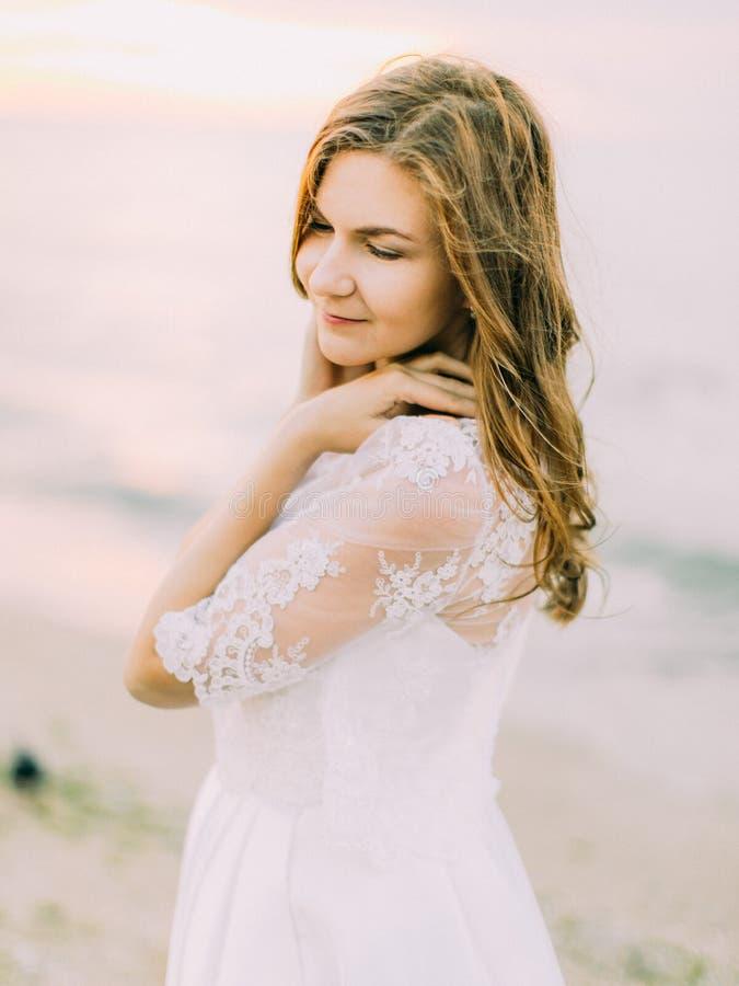 A noiva está tocando em seus ombros no fundo do mar O retrato lateral imagens de stock royalty free