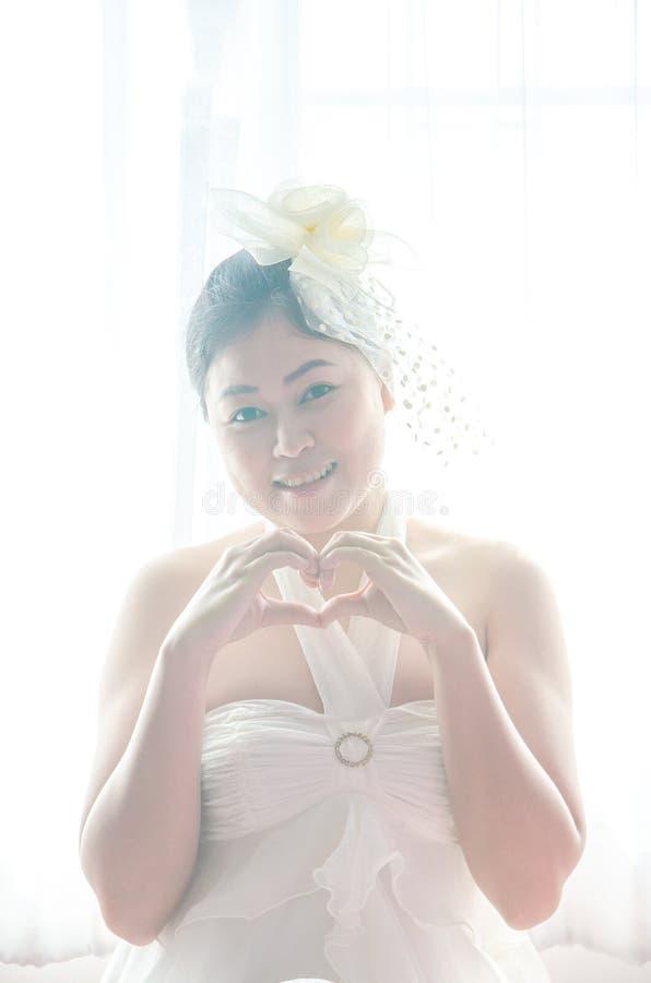 Noiva fêmea do retrato com as mãos que dão forma a um símbolo do coração no fundo do branco da janela fotografia de stock