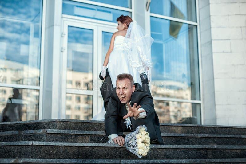 A noiva faz o noivo para casar-se fotografia de stock