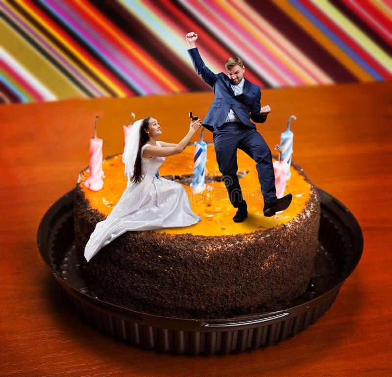 A noiva faz a oferta ao noivo no bolo grande fotografia de stock royalty free