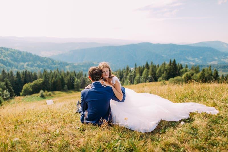 Noiva feliz nas mãos de seu noivo loving que senta-se na grama amarela no campo ensolarado com o Forest Hills majestoso como o fu fotografia de stock