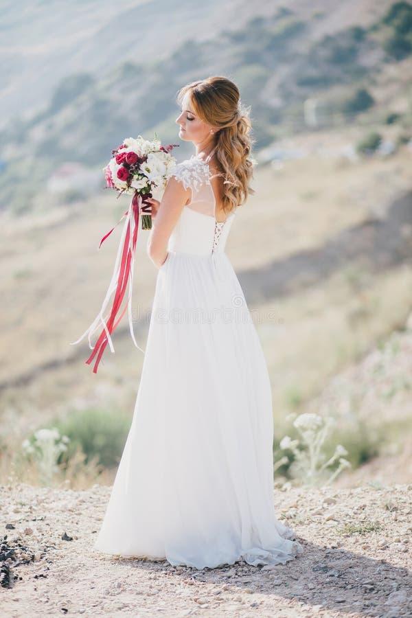 Noiva feliz nova bonita que está na parte superior da montanha imagens de stock royalty free