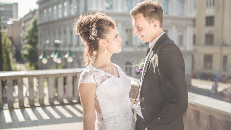 A noiva feliz nova dos pares do casamento encontra o noivo em um dia do casamento Recém-casados felizes no terraço com vista lind imagens de stock royalty free
