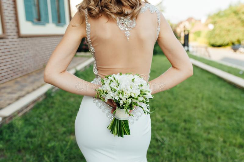 A noiva golpeia-a de volta ao quadro e guarda-a um ramalhete de flores coloridas fotos de stock