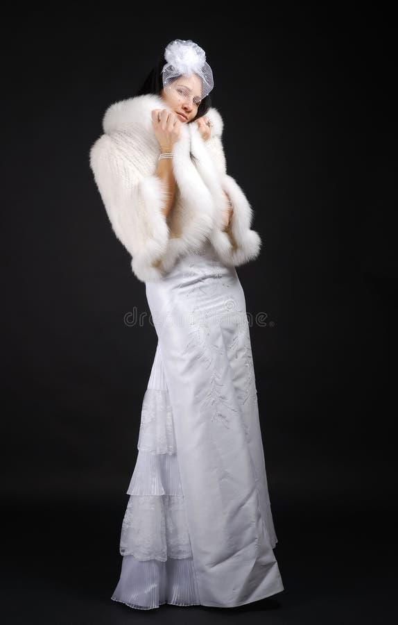 Noiva graciosa que envolve acima no casaco de pele. imagens de stock