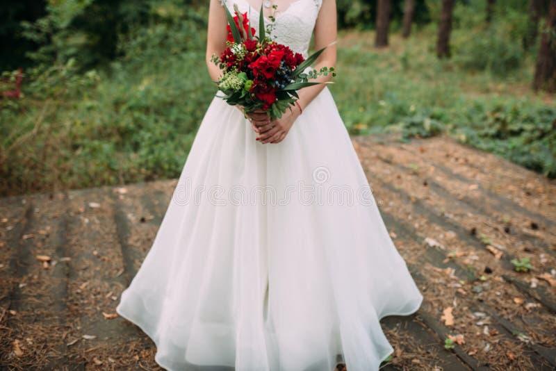 A noiva guarda o ramalhete do casamento com flores e verdes de Borgonha fotografia de stock