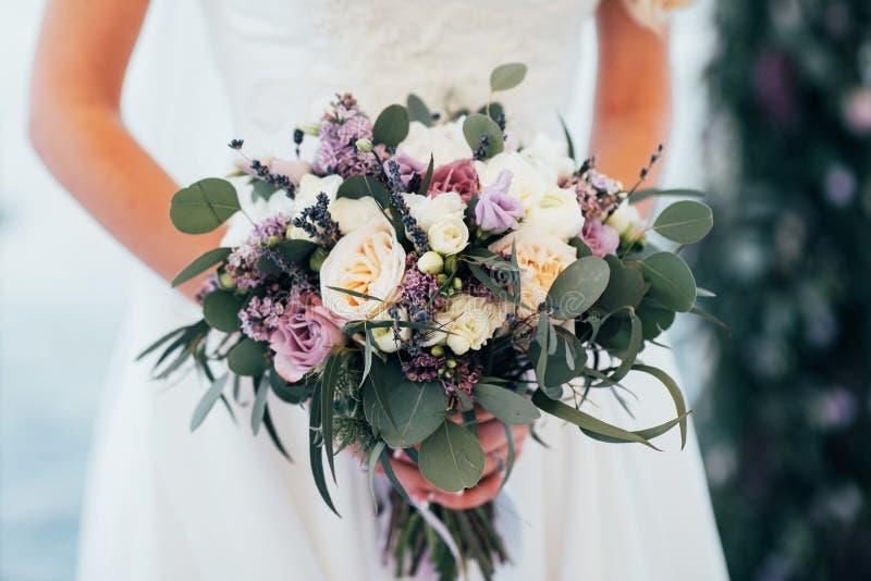 A noiva guarda um ramalhete em suas mãos perto do arco do casamento imagens de stock royalty free