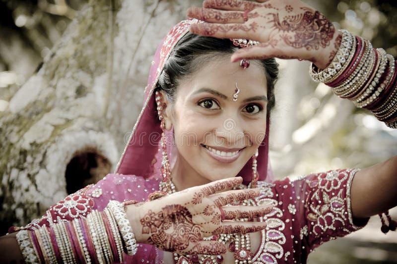Noiva hindu indiana bonita nova que está sob a árvore com as mãos pintadas levantadas