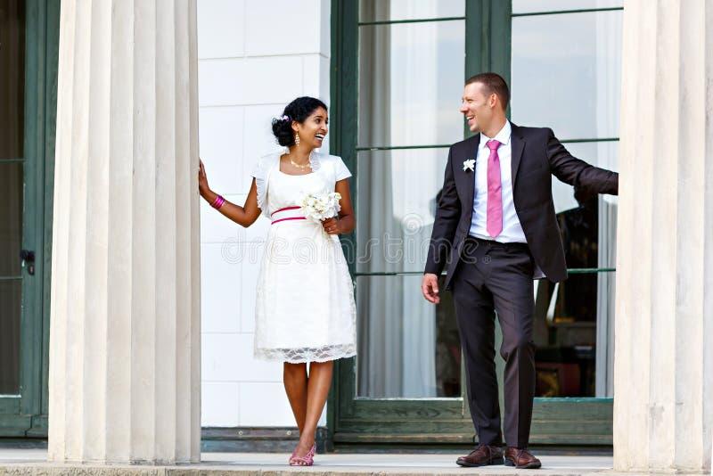 Noiva indiana bonita e noivo caucasiano, no parque do verão Flores felizes da terra arrendada da mulher nova Homem novo que sorri imagens de stock