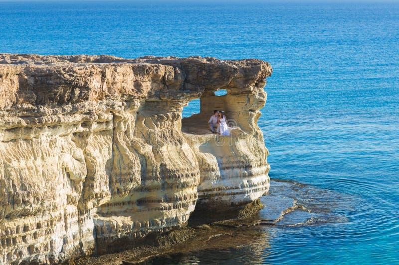 Noiva lindo bonita e noivo à moda em rochas, no fundo de um mar, cerimônia de casamento em Chipre fotografia de stock