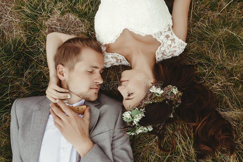 Noiva lindo e noivo à moda que encontram-se na parte superior, fim acima, boho nós fotografia de stock