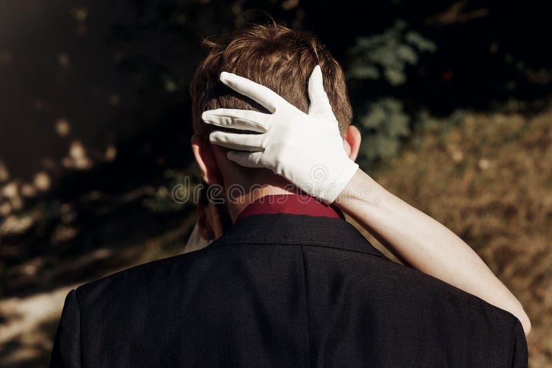 Noiva lindo elegante que abraça o noivo à moda mão no glov branco fotografia de stock