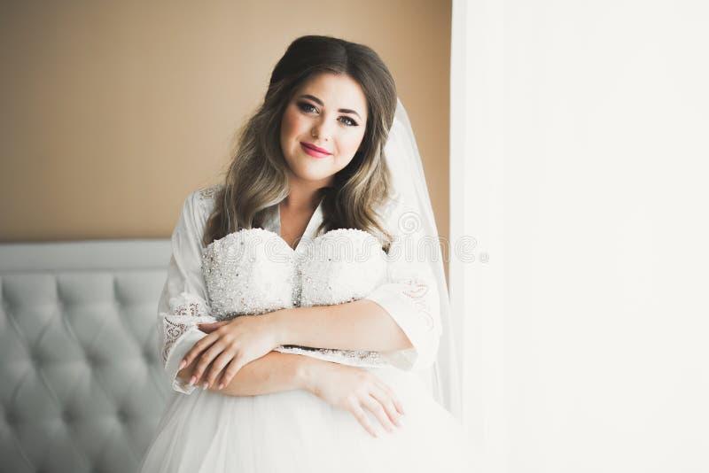 Noiva lindo na veste que levanta e que prepara-se para a cara da cerim?nia de casamento em uma sala fotos de stock