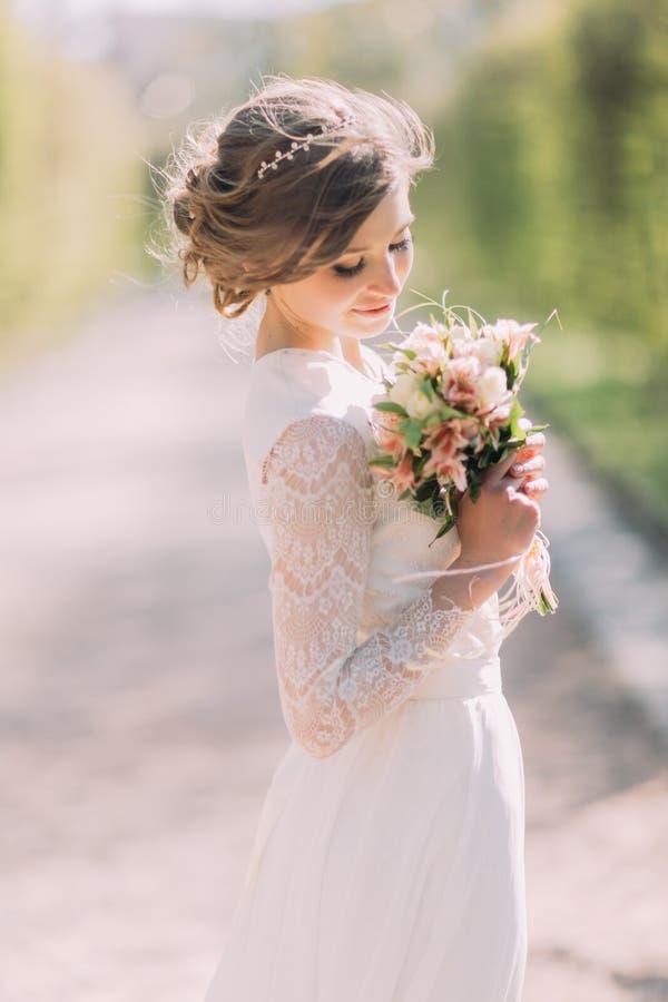 A noiva loura bonita com o ramalhete da mola floresce exterior foto de stock