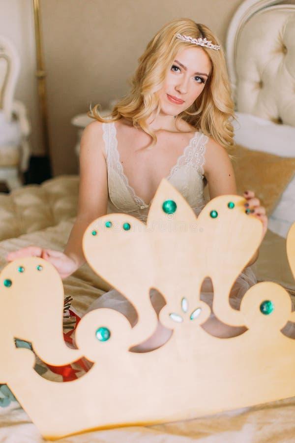 Noiva loura bonita que senta-se na cama com a coroa feito à mão grande nas mãos foto de stock royalty free