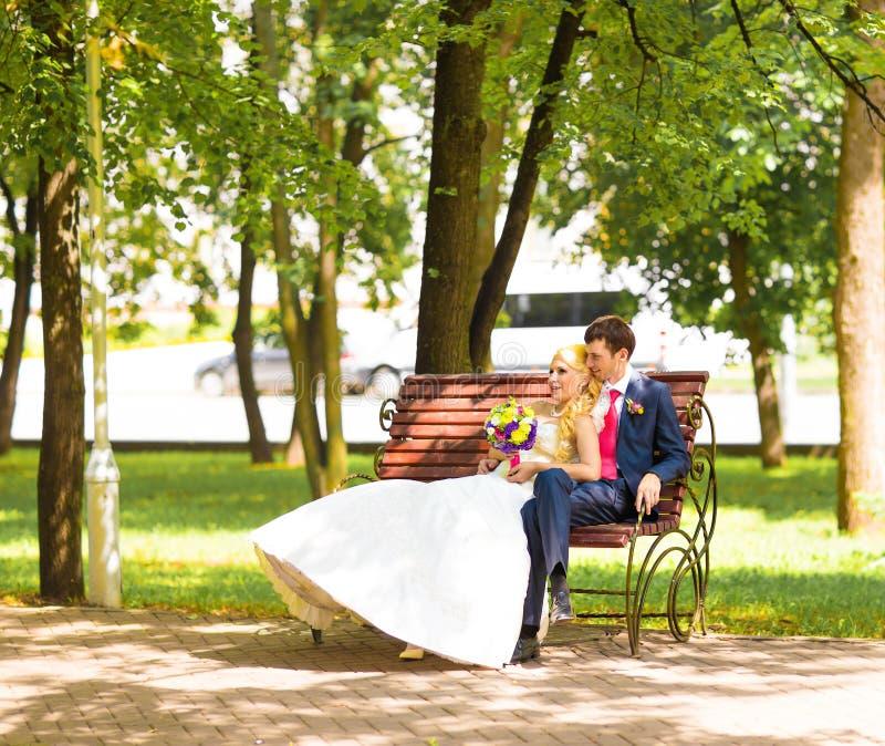 Noiva loura dos pares à moda do casamento no vestido branco e no noivo elegante que sentam-se em um banco no parque imagem de stock